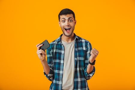 Excited young man wearing plaid shirt standing isolated over orange background, playing games on mobile phone