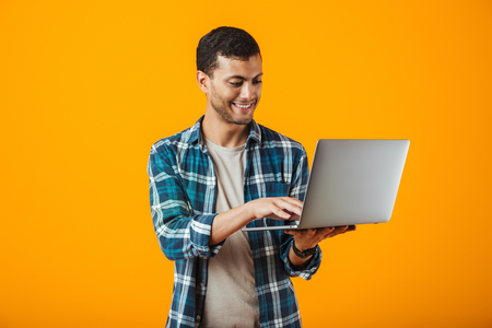 Cheerful young man wearing plaid shirt standing isolated over orange background, holding laptop computer