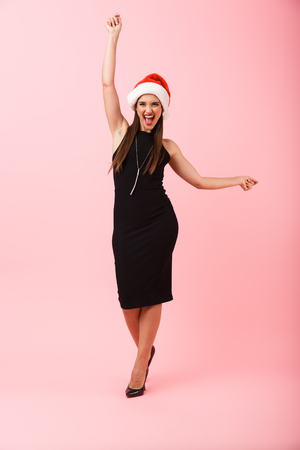 Full length portrait of a cheerful young woman wearing dress celebrating Christmas isolated over pink background, dancing