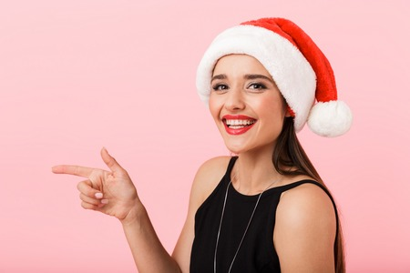 Happy young woman wearing Christmas hat celebrating isolated over pink background, pointing away