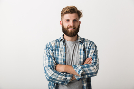 Happy bearded man dressed in plaid shirt standing isolated over white background, arms folded