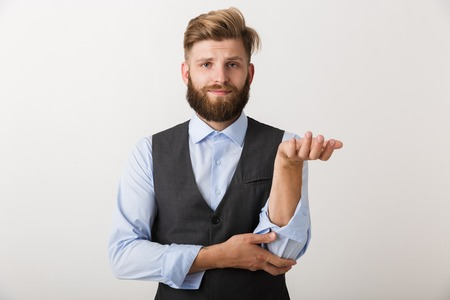 Confused young business man standing isolated over white background, shrugging shoulders