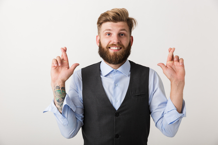 Image of a handsome nervous young bearded man standing isolated over white wall background make hopeful please gesture.
