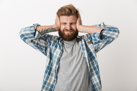 Annoyed bearded man dressed in plaid shirt standing isolated over white background, covers ears