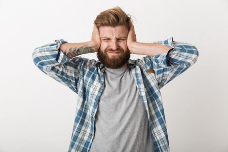 Verärgerter bärtiger Mann in kariertem Hemd, der isoliert auf weißem Hintergrund steht, bedeckt die Ohren Standard-Bild
