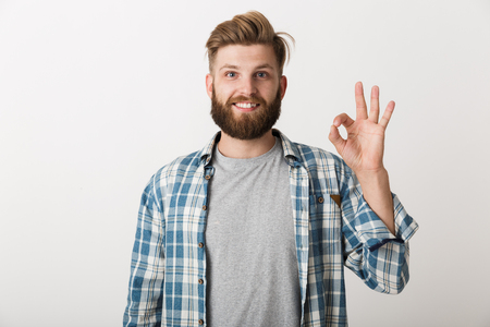Happy bearded man dressed in plaid shirt standing isolated over white background, showing ok 스톡 콘텐츠