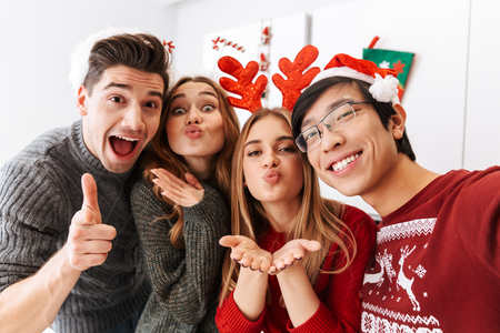 Group of cheerful multiethnic people celebrating New Year and taking selfie photo together Archivio Fotografico