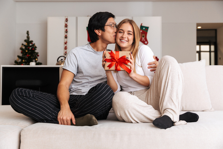 Cheerful young couple sitting on a couch at home, showing present box, kissing