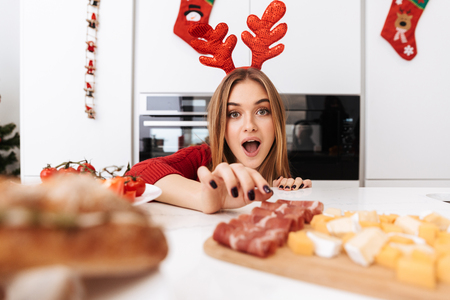 Excited pretty girl celebrating Christmas, wearing raindeer horns, eating food from a table Stock Photo