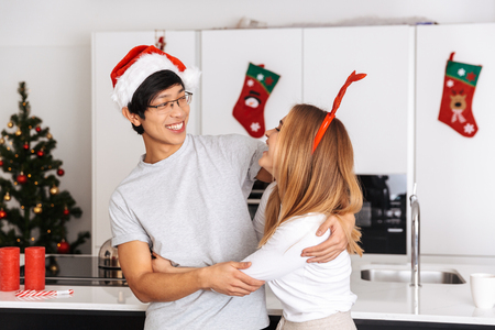 Image of smiling couple man and woman wearing christmas outfit standing in bright kitchen and hugging together Stock Photo