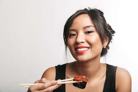 Pretty happy asian woman sitting isolated over white background, eating sushi with chopsticks