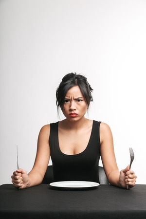 Upset asian woman sitting at the table with an empty plate isolated over white background, ready to eat