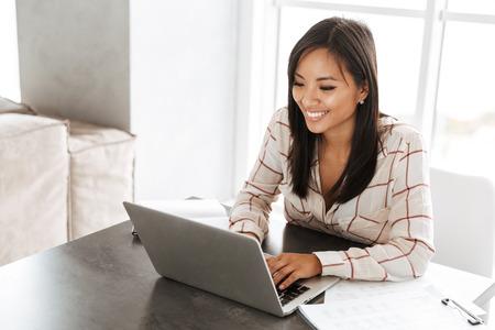 Bild einer asiatischen schönen Frau der 20er Jahre, die am Laptop arbeitet, während sie am Tisch drinnen sitzt Standard-Bild