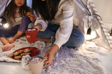 Photo of beautiful asian family mother and daughter eating cookies while sitting together at home in children playing tent Imagens