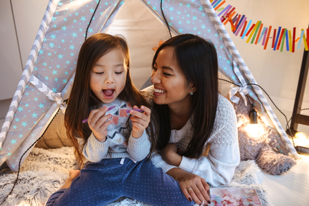 Photo of a happy young asian woman with her little daughter having fun on floor. Christmas concept. Stock Photo