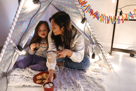 Photo of happy asian family mother and daughter eating cookies while resting together at home in children playing tent