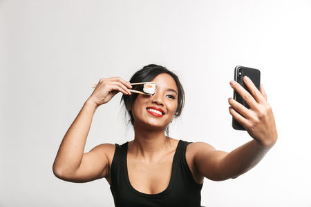 Cheerful young asian woman eating sushi with chopsticks isolated over white background, taking a selfie