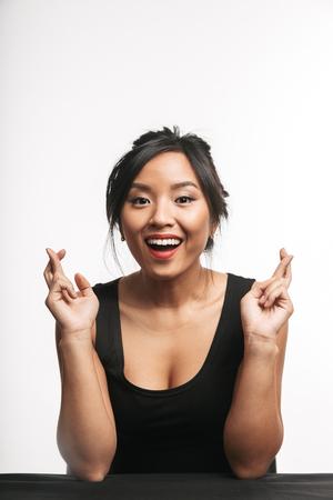 Mooie jonge Aziatische vrouw zittend aan de tafel geïsoleerd op een witte achtergrond, met de vingers gekruist voor geluk