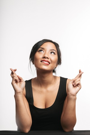 Pretty young asian woman sitting at the table isolated over white background, holding fingers crossed for good luck