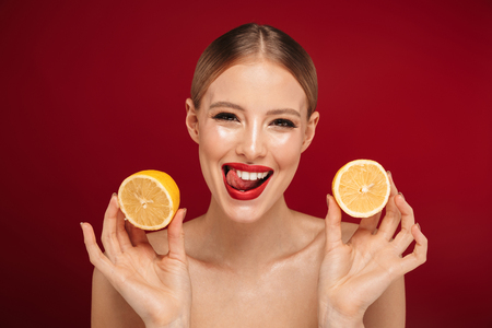 Beauty portrait of a pretty young topless woman wearing makeup isolated over red background,showing sliced orange 스톡 콘텐츠