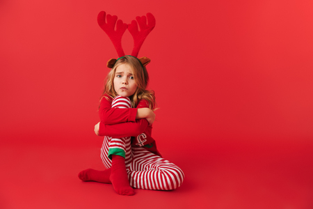 Upset little girl wearing Christmas raindeer costume sitting isolated over red background