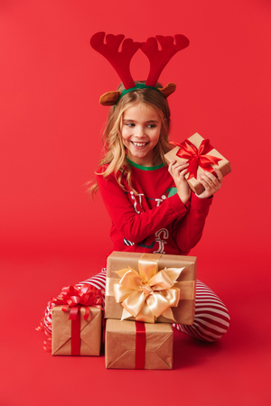 Cheerful little girl wearing Christmas raindeer costume sitting with stack of gift boxes isolated over red background