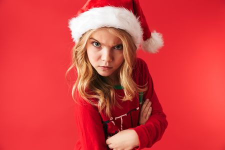 Upset little girl wearing Christmas costume standing isolated over red background, looking at camera
