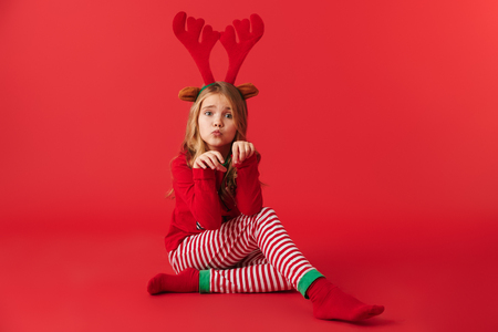 Cheerful little girl wearing Christmas raindeer costume sitting isolated over red background Stock Photo