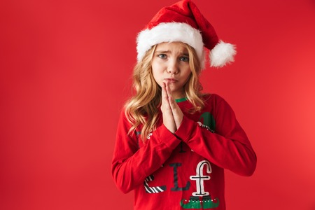 Sad little girl wearing Christmas hat standing isolated over red background, begging for a gift