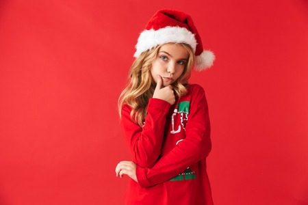 Pensive little girl wearing Christmas costume standing isolated over red background