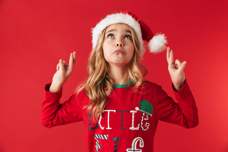 Sad little girl wearing Christmas hat standing isolated over red background, fingers crossed for good luck