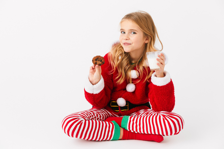 Cheerful little girl wearing Christmas costume sitting isolated over white background, eating cookie with milk Stock Photo