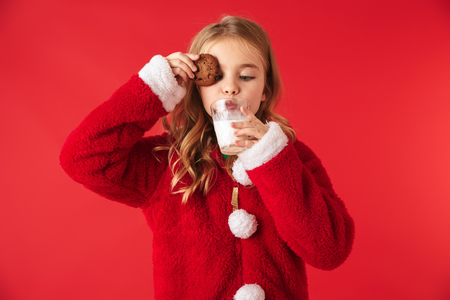Cute cheerful little girl wearing Christmas costume isolated over red background, drinking milk from a glass, eating cookies Stock Photo