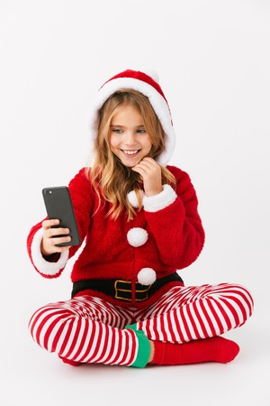 Cute cheerful little girl wearing Christmas costume isolated over red background, holding mobile phone, taking a selfie Stockfoto
