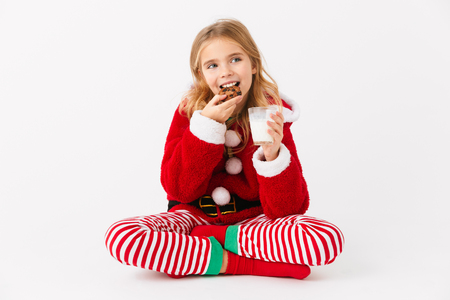 Cheerful little girl wearing Christmas costume sitting isolated over white background, eating cookie with milk 版權商用圖片
