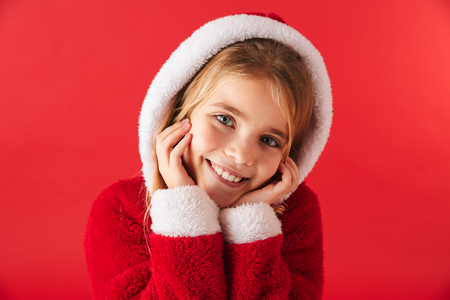 Cute cheerful little girl wearing Christmas costume isolated over red background Stock Photo