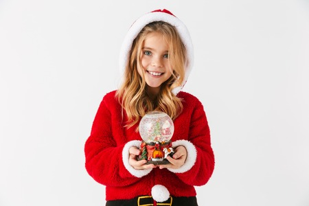 Cheerful little girl wearing Christmas costume sitting isolated over white background, holding a snow globe Stock Photo