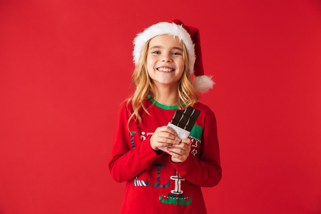 Cheerful little girl wearing Christmas costume standing isolated over red background, eating chocolate