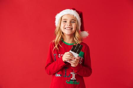 Niña alegre vistiendo traje de Navidad que se encuentran aisladas sobre fondo rojo, comiendo chocolate