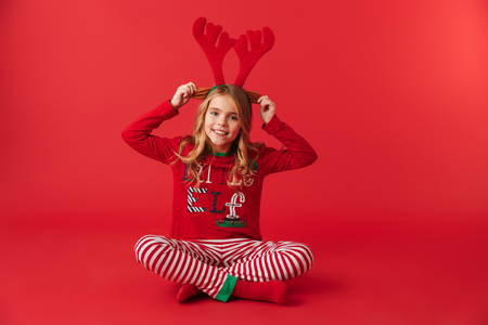 Cheerful little girl wearing Christmas raindeer costume sitting isolated over red background Stock Photo