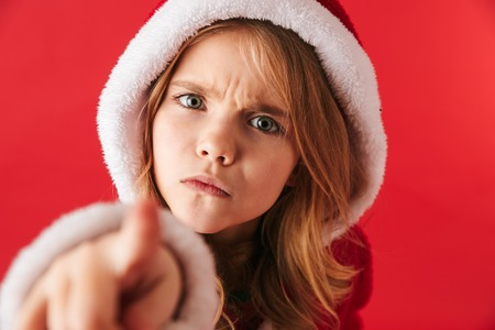 Upset little girl wearing Christmas costume standing isolated over red background, pointing at camera