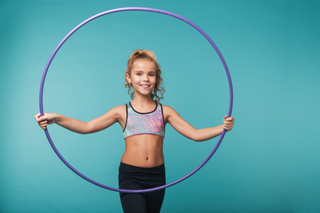 Cheerful little sports girl doing exercises with a hula hoop isolated over blue background