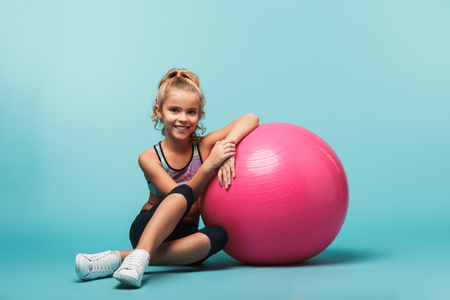 Wesoła dziewczynka nosi sportowe ubrania, opierając się na piłce fitness odizolowanej na niebieskim tle