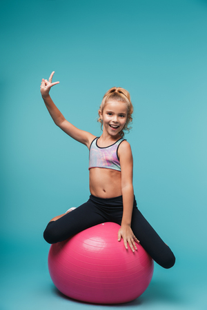 Cheerful little girl wearing sport clothes doing exercises with fitness ball isolated over blue background