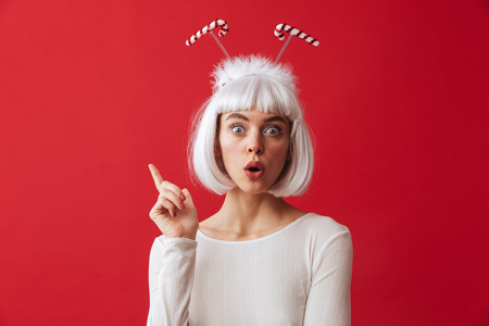 Image of a shocked young woman wearing christmas carnival costume pointing over red wall.