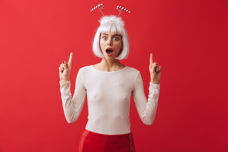 Image of a shocked excited young woman wearing christmas carnival costume over red wall pointing. Stock Photo