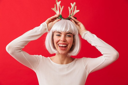 Image of a cute funny woman isolated over red wall background wearing deer ears costume carnival.