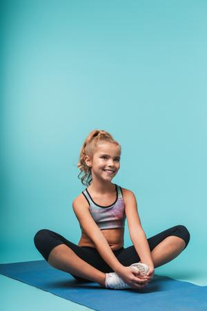 Vrolijk jong sportmeisje dat op een fitnessmat zit en yoga-oefeningen doet die over blauwe achtergrond worden geïsoleerd
