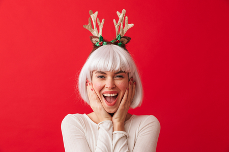Image of a young happy woman dressed in carnival christmas costume posing isolated over red wall background.
