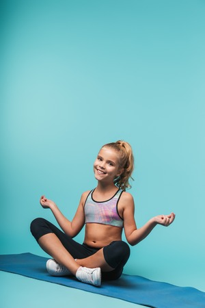 Cheerful young sports girl sitting on a fitness mat doing yoga exercises isolated over blue background